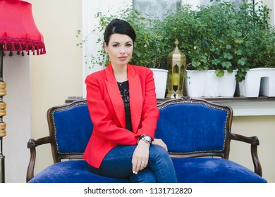 The stylish girl sits on the blue sofa