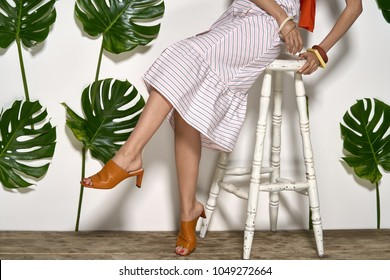 Stylish girl sits on a white stool on a wooden platform in a studio on a background of a white wall with big green leaves. She wears a striped pink dress, bracelets and brown mule shoes. Closeup.