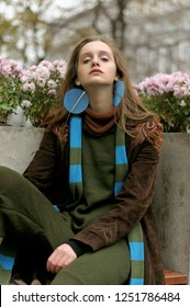Stylish girl sitting on a background of flower pots. She is dressed in a boho style: a brown raincoat, a green jumpsuit and a long blue scarf.