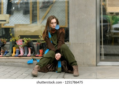 Stylish girl sitting at the window of the stock store. She is dressed in a boho style: a green jumpsuit and a long blue scarf.