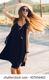 Stylish girl standing near road wearing short black dress, straw hat, black eyeglasses, and black backpack. She smiles and dances in the warm rays of setting sun.