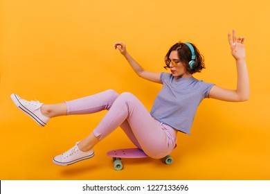 Stylish girl with tattoo sitting on longboard in studio. Pleasant female model with short curly hair posing on skateboard and listening music.