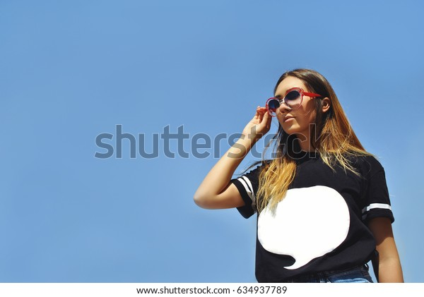stylish girl in trendy glasses on a blue background. Sunny day. the trend of the season. hair windblown.