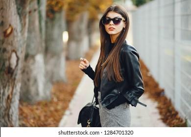 stylish girl walking through the city on a warm sunny autumn day