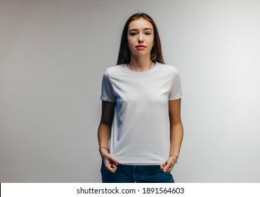 Stylish girl wearing white t-shirt posing in studio