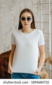 Stylish girl wearing white t-shirt and sunglasses posing in studio