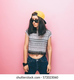 Stylish girl in yellow cap, shirt and denim. 90s fashion