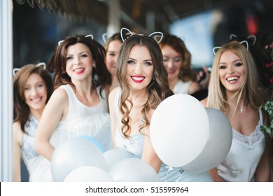 The stylish girls with ballons stand in the center of town