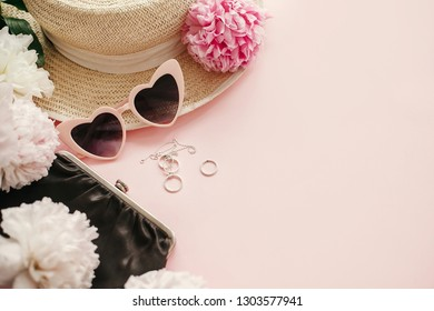 Stylish girly pink retro sunglasses,peonies, jewelry, hat, purse on pastel pink paper with copy space.  Hello spring concept. Summer vacation. International Women's Day