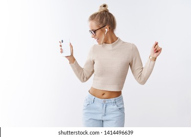 Stylish glamour and carefree caucasian woman in cropped sweater glasses turning away joyfully waving hands in dance holding smartphone listening music in wireless earbuds over white background