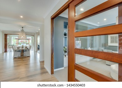 A stylish glass door with wooden frame giving entrance to a room leading to the dining area with a stylish dining table with a chandelier hanging over it.