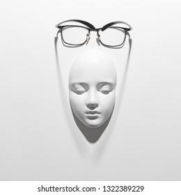 Stylish glasses with black frame or reading daily life on a gypsum face sculpture on a white background, soft long shadows, place for text. Flat lay