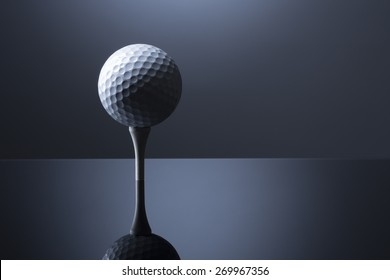 Stylish golf ball on tee isolated on dark blue background with reflection, copy space for text.