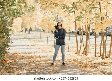 Stylish gorgeous young female photographer in a blue raincoat, jeans, , and sunglasses holds the camera in bent hand and waits for the model in the sunny forest in the afternoon