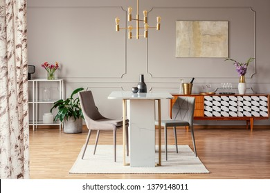 Stylish gray dining chairs by an elegant marble table with golden frame in a classy apartment room interior with gray walls