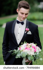 Stylish groom in black suit stands with a pink wedding bouquet
