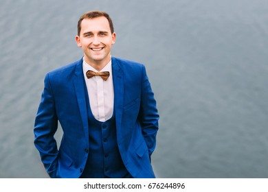 Stylish groom in blue suit, waistcoat and brown bow tie holding his hands inside the pockets and looking into the camera