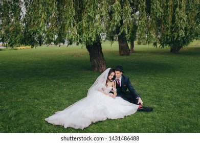 Stylish groom in a hat embraces a beautiful brunette bride with curly hair sitting under a willow. Portrait of newlyweds in love.