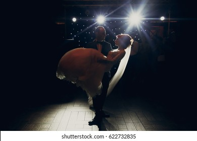 stylish groom lifting happy bride and  dancing at wedding reception in light. gorgeous wedding couple performing first dance in restaurant. newlyweds, emotional moment. space for text