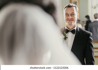 stylish groom looking at his gorgeous bride in stylish dress with amazing bouquet posing in luxury room in hotel. beautiful woman holding flowers and looking at groom. romantic moment
