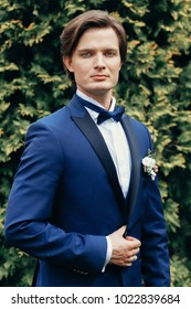 stylish groom portrait in park. handsome man in blue suit posing in spring park. gentleman or businessman at reception outdoors