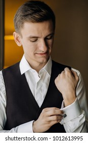 stylish groom portrait at the window while getting ready in the morning for wedding ceremony.
