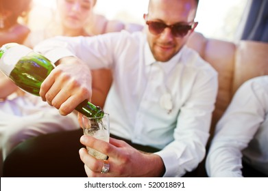 Stylish groomsman or best man of groom and bridesmaids  inside limousine at wedding party pours champagne in glasses.