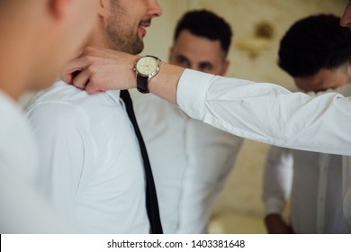 stylish groomsmen helping happy groom getting ready in the morning for wedding ceremony. luxury man in suit in room. space for text. wedding day