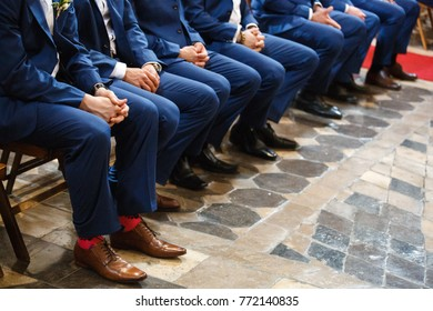 Stylish groomsmen sit during the ceremony in the church.