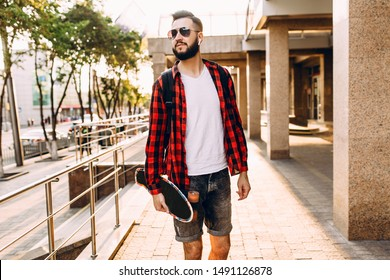 Stylish guy with a beard in wireless headphones walks around the city with a skateboard and listens to music