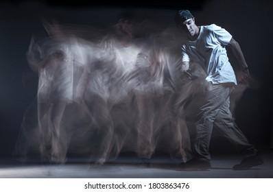 Stylish guy breakdancer dancing hip-hop in studio on black background. Long exposure shot