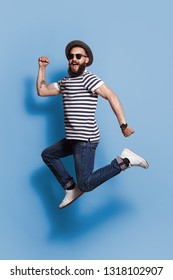 Stylish guy in hat and sunglasses jumping expressively high above ground on blue backdrop