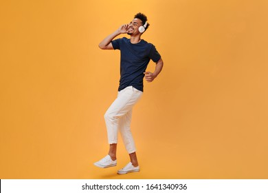 Stylish guy rhythmically moves and enjoys music in headphones. Man in white pants and blue shirt dancing on orange background