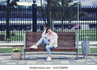 Stylish guy sitting on the street in a denim jacket on bench