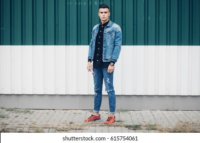 Stylish guy standing street in a denim jacket against, men's looks