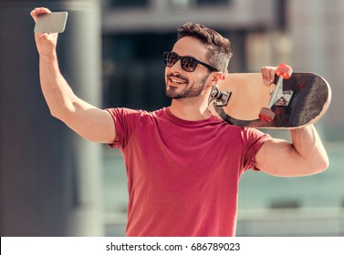 Stylish guy in sun glasses is holding a skateboard, doing selfie using a smart phone and smiling while walking outdoors