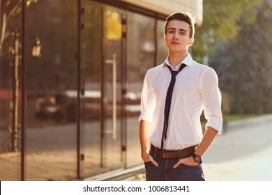Stylish guy a teenager in a white shirt and tie is standing on the mall near the store.