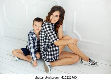 stylish guys in plaid dress posing to the camera. mom and son. amazing model. woman and boy