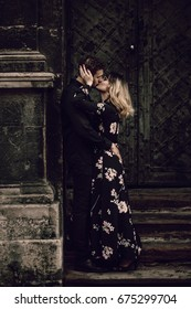 stylish gypsy couple in love kissing in evening city street at old building. woman and man embracing, romantic french atmospheric moment. love mood. modern bride and groom