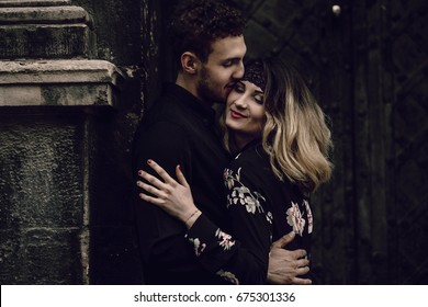 stylish gypsy couple in love kissing in evening city street at old building. woman and man embracing, romantic french atmospheric moment. love mood. unusual bride and groom