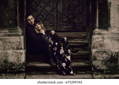 stylish gypsy couple in love posing in evening city street at old building. woman and man embracing, romantic french atmospheric moment. love mood. modern bride and groom