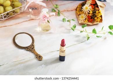 Stylish hand mirror with lipstick.