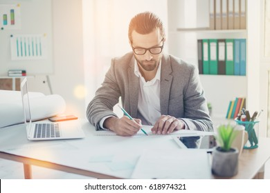 Stylish handsome concentrated man  in formal wear has ideas and working with blueprint papers and drawings in modern lightful office