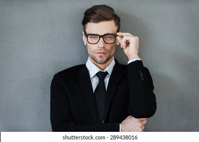Stylish handsome. Confident young businessman adjusting his eyewear and looking at camera while standing against grey background