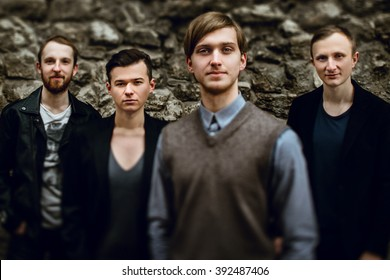 stylish handsome group of confident and successful men standing  on the background of city street