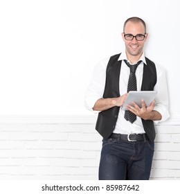 Stylish handsome guy leaning on wall with touchpad