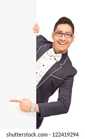 Stylish handsome guy pointing with finger on a blank panel isolated on white background