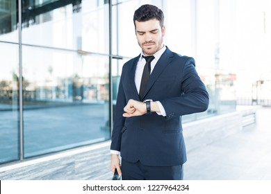 Stylish and handsome Latin businessman checking the time on his watch in city