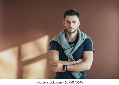 Stylish handsome man portrait with crossed arms posing on brown background. Copy space