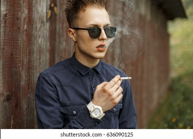 Stylish handsome man smoking a cigarette near a vintage wall